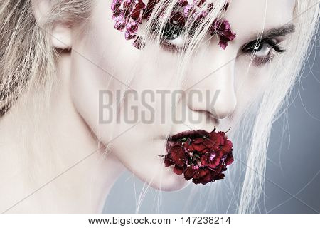 Beautiful girl, isolated on a dark-blue background with varicoloured flowers on fase, emotions, cosmetics