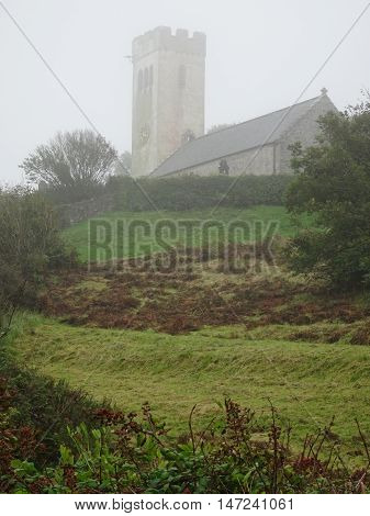 Church in rural landscape photographed at Manorbier in Pembrokeshire
