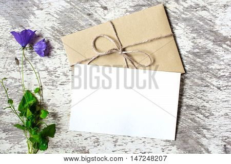 Blank white greeting card and envelope with blue wildflowers on white rustic wood background with copy space for creative work design