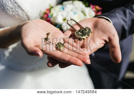 Decorative wedding lock and keys with coulomb in hands of newlyweds.