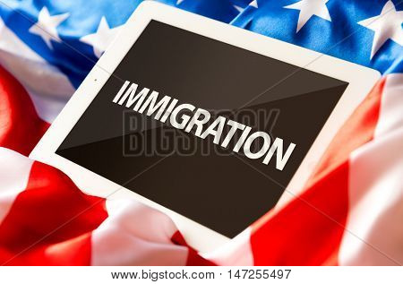 Immigration on tablet and the US flag