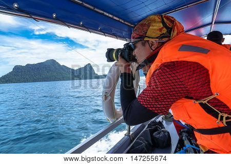 Semporna,Sabah-Sep 10,2016:Unidentified professional photographer using a professional DSLR camera at Semporna,Sabah.Semporna is surrounded by white sand & the turquoise waters of the Celebes Sea.