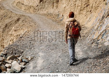 Male Traveler Walking Uphill On Driveway Sand Dune - Upcountry Journey And Travel Concept