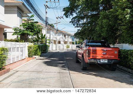 THAILAND - 14 SEP - Orange car parked block the main road in village under tree shade in Pattaya, Thailand on September 14, 2016
