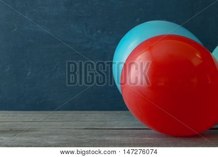 Balloons close up on wooden table with free place
