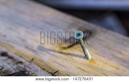 Screw on old wooden desk. Shallow DOF