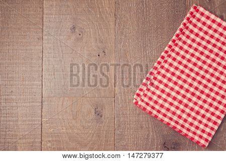 Abstract wooden texture background with red checked tablecloth. View from above