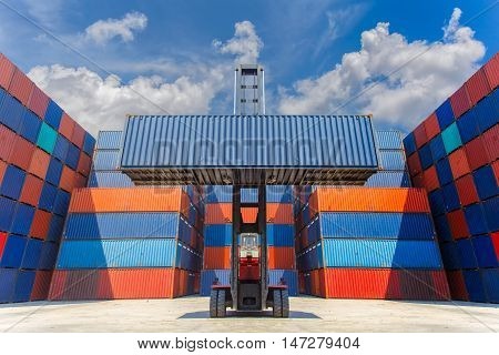 Forklift truck lifting cargo container in shipping yard for transportation import export and blue sky background