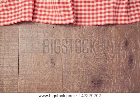 Background with red checked tablecloth and wooden board. View from above