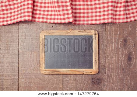 Abstract background with red checked tablecloth and chalkboard. View from above