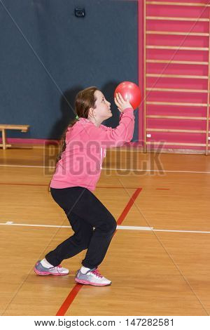 Nahariya, Israel, February 15 2016: Girl throws a red ball in the basket at the sports hall in Nahariya, Israel