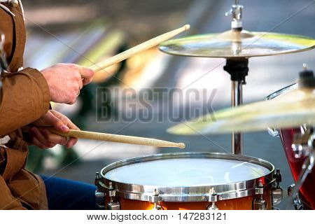 Music street performers on autumn outdoor. Middle section of body part. Visible hands with drumsticks