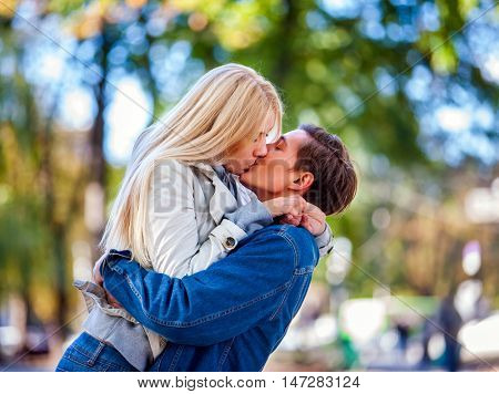 Young couple hugging and kissing in autumn park. Guy lift girl above autumn land.