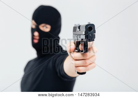 Man robber in balaclava pointing with gun
