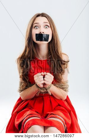 Frightened young woman bounded by ropes sitting with closed mouth by tape