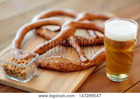 food, baking, cooking and pastry concept - close up of beer in glass, pretzels and peanuts on wooden table