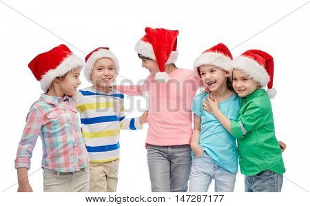 childhood, christmas, holidays, friendship and people concept - group of happy smiling little children in santa hats hugging