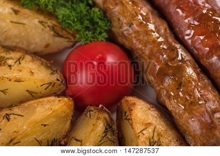 Delicious grilled wieners with fried potatoes and vegetables