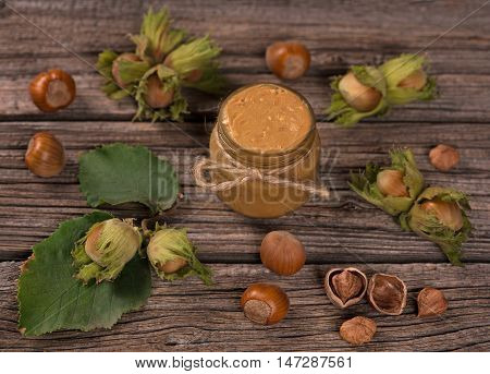 Ripe filberts and hazelnuts cream over old wooden background