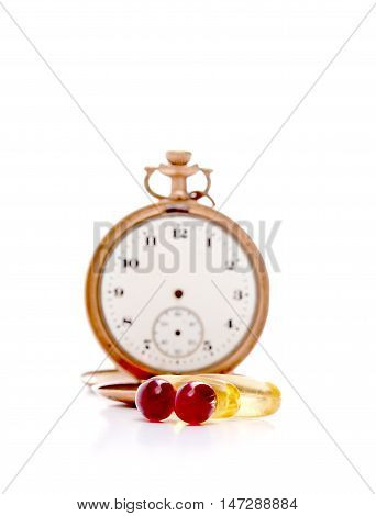 picture of a Cod liver oil omega 3 and krill oil gel capsules in front of vintage pocket clock