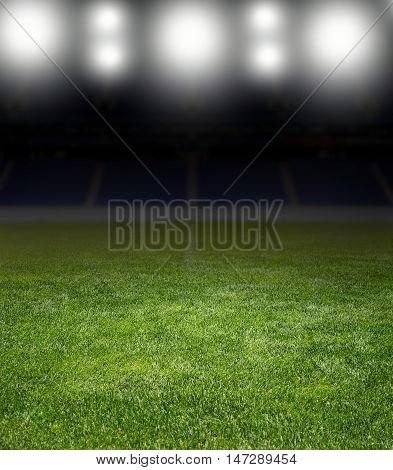 Green soccer field row of bright spotlights illuminated stadium in night