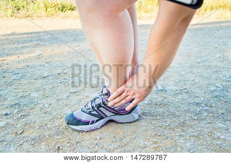 athlete runner touching the foot with pain due to sprained ankle
