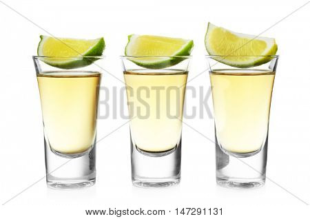 Shots of gold tequila with lime slice in a row isolated on white