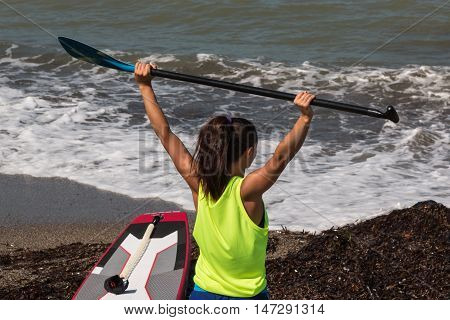 Girl Stretching Her Arm's Muscles With Oar Before Surfing, Stand Up Paddle
