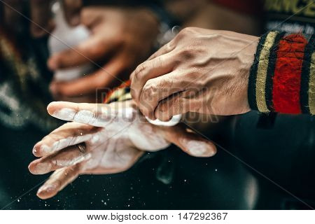 closeup of male hands with sports wristbands rubs chalk powder