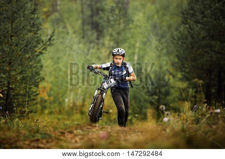 Revda Russia - July 31 2016: teen boy athlete mountainbike uphill on foot with his bicycle during Regional competitions on cross-country bike
