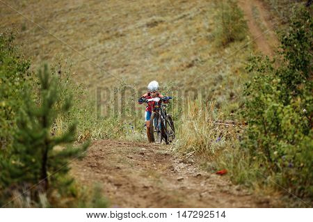 Revda Russia - July 31 2016: girl athlete mountainbiker rise step in mountain with my bike during Regional competitions on cross-country bike