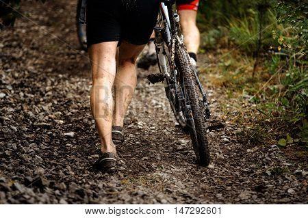 racer mountainbiker walks mountain next to bike. feet and wheel in mud