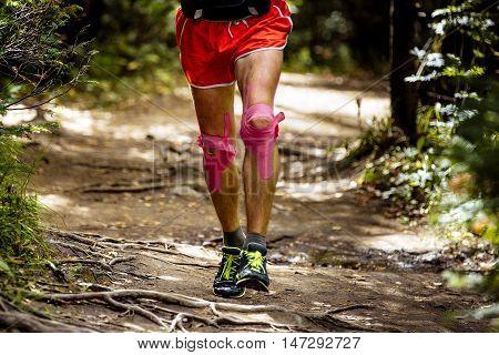 feet athlete runner his knees kinesio tape. running a marathon in forest tree roots
