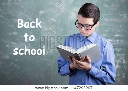 Schoolboy In Glasses Reading Book On The Background Of School Board With The Inscription