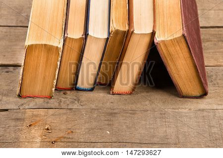 Old And Used Hardback Books Or Text Books On Wooden Table