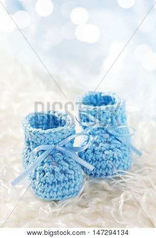 Blue baby crochet shoes on a white fur