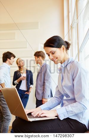 Young woman working with laptop in a meeting