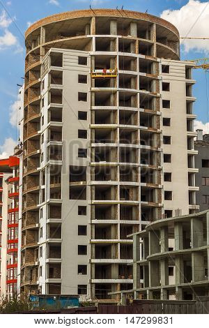 High multi-storey buildings under construction and cranes against blue sky