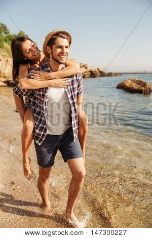 Handsome young man giving piggy back ride to his girlfriend at the beach
