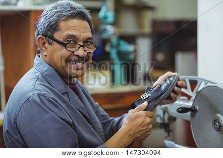 Portrait of shoemaker using sewing machine in workshop