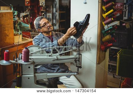 Shoemaker examining a shoe in workshop