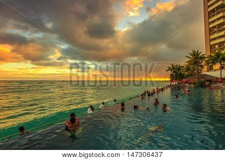 Waikiki Oahu Hawaii - August 20 2016: people of infinity edge swimming pool looking at the ocean twilight. Sheraton Waikiki Hotel in Waikiki Beach Honolulu. Summertime relaxing in luxury resort.