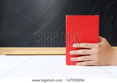 red book in hand against a background of black school board / necessary literature for education