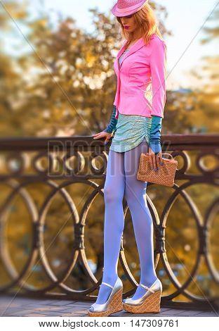 Fall Fashion. Urban Model Woman. Creative fashion Outfit. Glamor Stylish Heels, Hat Trendy fashion Handbag Pantyhose. Playful Hipster Redhead girl Enjoy nature. Autumn Outdoor Park background. Fashion