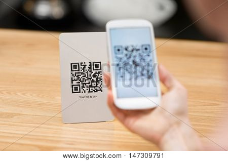Closeup of a hand holding phone and scanning qr code. Woman hand paying with qr code. Close up of customer hand making payment through smart phone and scan code.