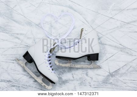 I love ice skating. Ice skates on rink background with lace in heart shape.