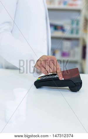 Pharmacist swiping card through payment terminal in pharmacy