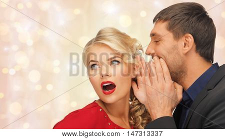 people, communication, gossiping, christmas and information concept - close up of man and woman spreading gossip over holidays lights and snow background