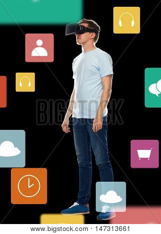 3d technology, gaming, augmented reality, cyberspace and people concept - happy young man in virtual reality headset or 3d glasses with menu icons over black background