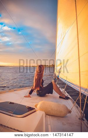 girl with long brunette hair sitting at the stern of the yacht and looks into the distance at sunset, sunrise